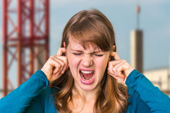 Woman covering her ears to protect from loud noise. Unhappy woman covering her ears to protect from loud noise Royalty Free Stock Image