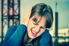 Woman covering her ears to protect from loud noise. Unhappy woman covering her ears to protect from loud noise - retro style royalty free stock photo