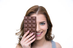 Woman covering her eye with chocolate bar Royalty Free Stock Photos