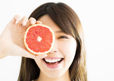 Woman covering her eye with grapefruit. Happy Woman covering her eye with grapefruit stock images