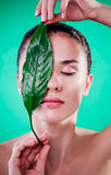 Woman covering her eyes with a leaf. Organic cosmetics concept Stock Photography