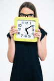 Woman covering her face with big clock Stock Image