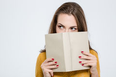 Woman covering her face with book Stock Images