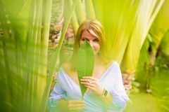 Woman covering her face with green leaf royalty free stock images