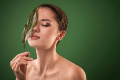 Woman covering her face with a leaf. Organic cosmetics concept Royalty Free Stock Images