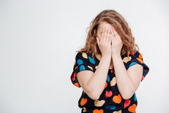Woman covering her face with palms. On a white background Stock Photos