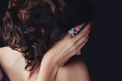 Woman, covering her face, a supphire ring. A luxurios stunning woman with gorgeous hair covering her face, her delicate hand with nails painted  red, and a large Royalty Free Stock Photo