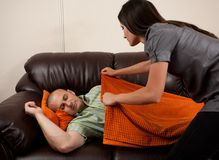 Woman covering her husband with a blanket. Young woman putting a blanket on her exhausted husband asleep on the sofa Stock Photos