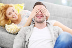 Woman covering her husband's eyes when watching tv Royalty Free Stock Images