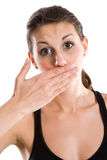 Woman covering her mouth. A young woman covers her mouth with her hand, with her eyebrows raised in surprise Stock Photo
