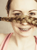 Woman covering her mouth with blonde braid. Young woman covering her mouth with blonde hair braid. Haircare and hairstyling concept Stock Image