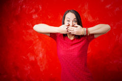 Woman covering her mouth with both hands Stock Images