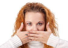Woman covering her mouth by the hand. Portrait of red-haired woman covering her mouth by the hands, over white background Stock Image