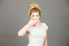 Woman covering her mouth with hand. Seeing something shocking, surprised and speechless face expression Royalty Free Stock Image