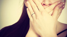 Woman covering her mouth with hand Royalty Free Stock Photography