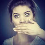Woman covering her mouth with hand Stock Photo