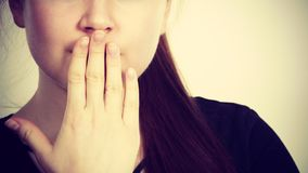 Woman covering her mouth with hand. Seeing something shocking, surprised and speechless face expression Stock Photo