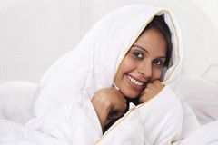 Woman covering herself with bed sheet Royalty Free Stock Images