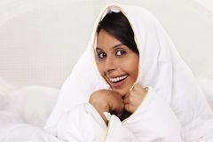 Woman covering herself with a bed sheet Royalty Free Stock Images