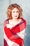Woman covering herself in a blanket. Smiling woman with red blanket Royalty Free Stock Image