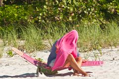 Woman covering herself from too much sun with a pink towel. And sitting on a folding chair in the sand of a tropical beach on the Gulf of Mexico on a hot Royalty Free Stock Images