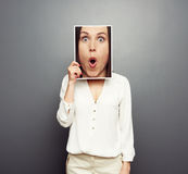 Woman covering image with big amazed face Royalty Free Stock Image