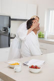 Woman covering man's eyes at breakfast table in kitchen Stock Image