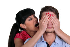 Woman covering a man's eyes Royalty Free Stock Images