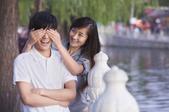 Woman Covering Mans Eyes by a Lake Royalty Free Stock Images