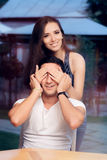 Woman Covering Man's Eyes Taking him by Surprise on a Blind Date Royalty Free Stock Images