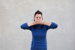 Woman covering mouth with hands. Young woman covering mouth with both hands in front of grey wall Royalty Free Stock Images