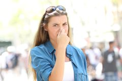 Woman covering nose in a contaminated city. Disgusted woman covering nose in the street of a contaminated city Stock Photo
