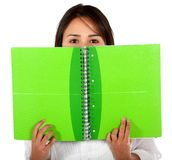 Woman covering with a notebook Royalty Free Stock Photography