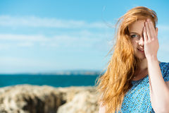 Woman covering one eye. Pretty young redhead woman covering one eye with her hand as she stands on a rocky seashore Stock Photography