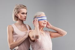 Confused senior lady taking off piece of fabric while serious unpleasant girl. Woman covering vision. Confused senior lady taking off piece of fabric while stock photography
