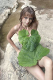 Woman covers body with burdock leaves Stock Photo