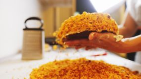 Woman covers creamy cake with crumbles at bakery closeup