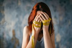 Woman covers face, hands tied with measuring tape. Woman covers face with her hands tied with measuring tape. Fat or calories burning concept. Weight loss Royalty Free Stock Image