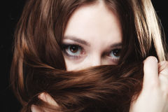 Woman covers the face by long brown hairs Royalty Free Stock Images