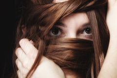 Woman covers the face by long brown hairs Stock Image