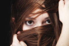 Woman covers the face by long brown hairs Royalty Free Stock Image