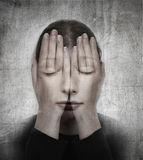 Woman covers her face with her hands on the grunge backround. Stock Photos