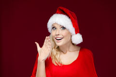 Woman covers her mouth with hand. Woman in Christmas cap covers her mouth with hand, isolated on purple Stock Photos
