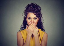 Woman covers her mouth with hands. Looking at camera Stock Photography