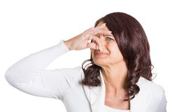 Woman covers her nose disgusted something stinks. Closeup portrait woman covers her nose disgusted something stinks, very bad smell situation isolated on white royalty free stock image
