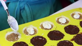A woman covers melted chocolate filling with crushed almond, which is in silicone form. Cooking candies, glazed in white and dark. Chocolate stock video