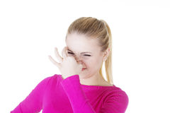 Woman covers nose with hand showing that something stinks. Isolated on white royalty free stock image