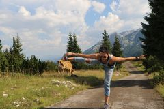 Woman with cow in the background. Woman practicing yoga on road with cow in the background. The picture was taken on Zabljak municipiun. The model was Royalty Free Stock Photography
