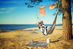 Woman in cow pajamas in a hammock Stock Photo