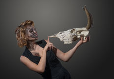 Woman with cow's skull in her hands, face to face Stock Photos